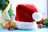 Composition with Santa Claus red hat and Christmas decorations on light background