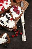 Bread with cottage cheese and berries on wooden board close-up