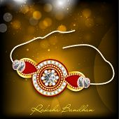 Beautiful rakhi on shiny brown background for Happy Raksha Bandhan celebrations.