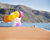 multicolored balloons tied to a dock on a windy day