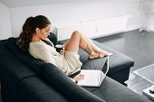 foto of morning  - Portrait of young woman sitting on sofa checking her emails - JPG