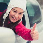 Smiling young pretty woman in the car - safe winter driving concept