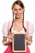Young woman in a dirndl holding up a blank slate