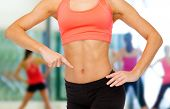 fitness, exercise and diet concept - close up of woman pointing finger at her six pack