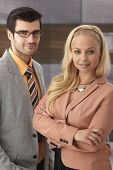 Closeup portrait of elegant young businesspeople standing in office.