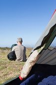 pic of sleeping bag  - Happy camper sitting outside his tent holding sleeping bag on a sunny day - JPG