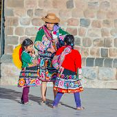 CUZCO, PERU, MAY 1, 2014 - Woman and two girls in regional attire. She is carrying a llama baby and