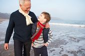 Grandfather And Grandson Walking On Winter Beach