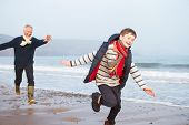 Grandfather And Grandson Running On Winter Beach