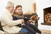 Grandmother And Granddaughter Relaxing At Home With Pet Dog