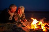 Senior Couple Sitting By Fire On Winter Beach