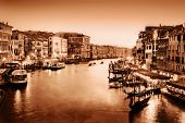 Venice, Italy. Gondola floats on Grand Canal, Italian Canal Grande at sunset. View from Rialto Bridg