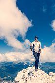 Female Climber Ascending A Mountain Top