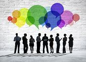 Group of business people discussing with colorful speech bubbles above them.