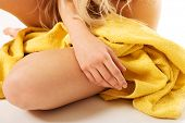 Close up on woman sitting wrapped in yellow towel.