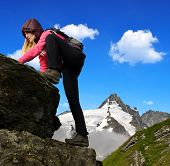 Girl on rock, in the background mount Grossglockner, National Park Hohe Tauern, Austria