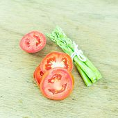 Close Up Green Asparagus And Slice Tomato On Wood Background