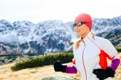 Young Woman Running In Mountains On Winter Sunny Day