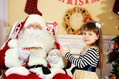 Little cute girl giving glass of milk to Santa Claus near Christmas tree at home