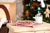 Cookies and milk for Santa on table, on beautiful Christmas interior background