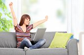 Happy woman working on laptop and gesturing happiness seated on a sofa at home