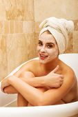 Woman sitting in bath with face mask and showing thumbs up.