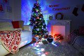 Beautiful Christmas interior with sofa, decorative fireplace and fir tree