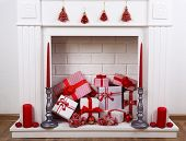 Fireplace with Christmas boxes and candles on wooden floor