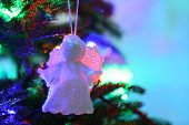 Knitted Christmas angel on Christmas tree, close-up