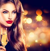 Sexy model girl with glass of champagne at party, drinking champagne over holiday glowing background. Beauty woman with perfect fashion makeup. Christmas and New Year holiday celebration