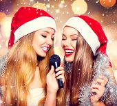 Christmas party, karaoke. Beauty girls in santa hat with a microphone singing and dancing over holiday glowing background. Disco. New year celebration