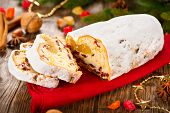 Christmas Stollen. Traditional Sweet Fruit Loaf with Icing Sugar. Xmas holiday table setting, decorated with garlands, baubles, wallnuts, hazelnuts, cinnamon sticks.
