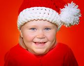 Closeup portrait of cute little baby girl wearing Santa hat isolated on red background, funny festive costume for Christmas celebration