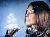 picture of snow queen  - Closeup portrait of beautiful snow queen with crown on head holding on hand magical glowing Christmas tree - JPG