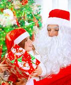 Portrait of cute little girl receives present from Santa Claus, sitting near decorated Christmas tree with beautiful wrapped gift box, happy winter holidays concept