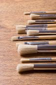 Row Of Paint Brushes On Wooden Table Background
