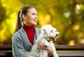 Smiling young woman with maltezer dog out in the park