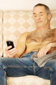 Shirtless handsome man on a sofa looking at his smartphone.