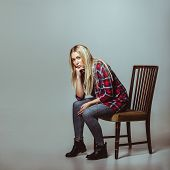 Young Woman In Casual Outfit Sitting On Chair