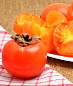 Ripe Persimmon Fruits On White Plate And Napking,  Sacking Background