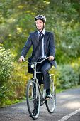 Full length of young businessman riding a bicycle to work