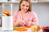 Smiling young woman  in kitchen  preparing food,  cutting carrot