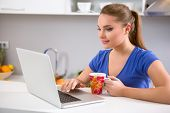 Woman using a laptop while drinking coffee in her kitchen