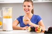 Beautiful woman using a blender with smoothie in the kitchen.