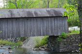 stock photo of covered bridge  - A gray covered bridge over a river in Vermont - JPG