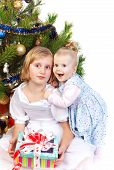 baby girl hugging her sister under the christmas tree isolated on white