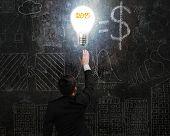 Businessman Touching 2015 Light Bulb Illuminated Dark Doodles Wall