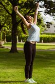 Side view of healthy and beautiful young woman stretching hands in park