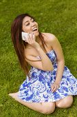 Cheerful young woman using mobile phone in the park