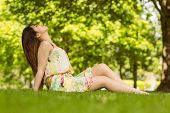 Full length side view of relaxed young woman sitting on grass at the park